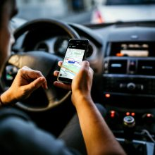 Mann im Auto am Handy mit GPS